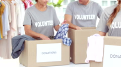 Smiling friends volunteers separating clothes - stock footage