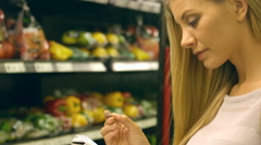 Woman checking her list while grocery shopping Stock Footage