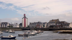Boats and lighthouse in village, France Stock Footage