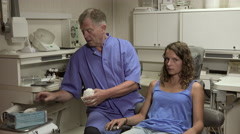 Dentist puts on his gloves near her patient - stock footage