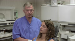 Dentist positions the chair of his patient - stock footage