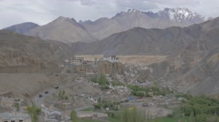 Trucks on highway through village with gompa and moonland,Lamayuru,Ladakh,India Stock Footage