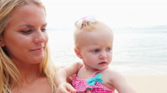 Blonde mother and baby on a beach Stock Footage
