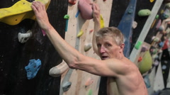 Mature man spending his time concentrating on his sport of climbing - stock footage