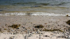 Calm waves fall on a rocky and sandy seashore Stock Footage