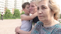 Grandson embracing grand father while three people family sitting outdoors Stock Footage