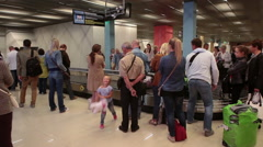 Arriving passengers claim checked-in baggage after disembarking from an airline  Stock Footage