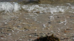 Calm waves fall on a rocky and sandy shore Stock Footage