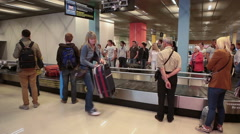 Passengers are in baggage claim area. A baggage carousel is full of bags Stock Footage