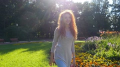4K Pretty red haired happy girl walking in park smiling. Steadicam. Stock Footage