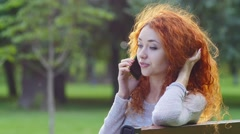 4K Pretty red haired happy girl talking by phone in park, smiling. Stock Footage