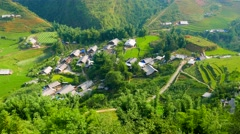 View of valley with green rice terraces and village. Sapa, Vietnam. Stock Footage