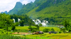 Ban Gioc Waterfall in lush green valley with rice fields. Vietnam, May 2015. Stock Footage