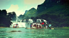 Stock Video Footage of Tourists on bamboo rafts cruising around the Ban Gioc Waterfall. Retro look.