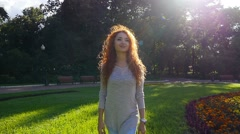 Pretty red haired happy girl walking in park smiling. Steadicam, slow motion. Stock Footage