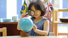 Little Asian student looking at globe with magnifying glass Stock Footage