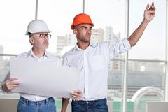 Cheerful builders are planning to build a new construction - stock photo