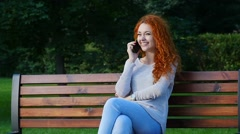 Pretty red haired happy girl talking by phone in park. Slow motion. Stock Footage