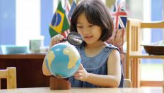 Little Asian student looking at globe with magnifying glass - stock footage