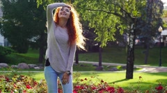 Pretty red haired happy girl has fun in park smiling. Slow motion. Stock Footage