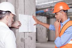 Cheerful skilled builders are solving construction problems Stock Photos