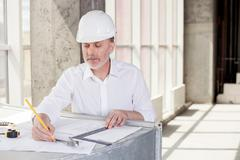 Skilled senior builder is planning new project - stock photo