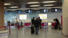 Passengers have registration at check-in counters in the lobby of airport hall - stock footage