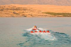 Kids tube riding tawed by speedboat. - stock photo