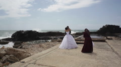 Muslim woman takes wedding photos of a couple next to the sea Stock Footage