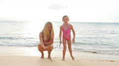 Blonde mother and daughter writing in sand on a beach Stock Footage