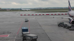 Aircraft lands into runway of apron and one stands in the servicing area Stock Footage