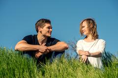 Young couple stitting on a grass - stock photo
