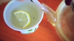 Put green tea in cup with  slice of lemon and teapot Stock Footage