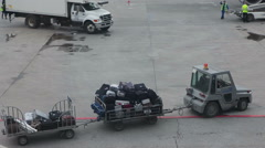 Truck with full luggage dollies drives to beltloader for loading baggage Stock Footage