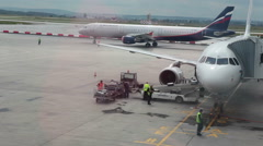 Beltloader is near departing aircraft for luggage loading into craft, airport Stock Footage