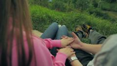 Young man takes womans hand on a background green grass Stock Footage