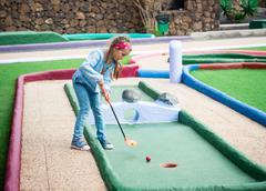 Little girl playing golf Stock Photos