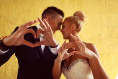 Bruide and groom making love sign with their hands Stock Photos
