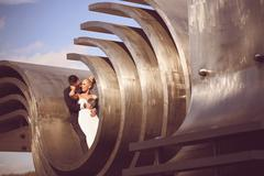 Bride and groom sitting on architectural metallic piece Stock Photos