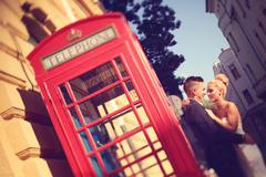 Bride and groom near phonebooth - stock photo