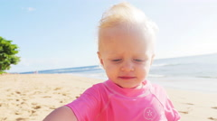 Cute blonde toddler's hat gets blown off on a beach Stock Footage