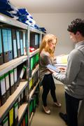 digitalization: young man and woman in the company archives - stock photo