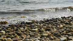 Slow motion of calm waves on rocky coastline Stock Footage