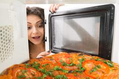 Girl open a microwave - stock photo