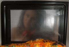 Cooking pizza in the microwave - stock photo