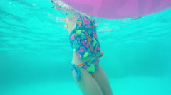 Cute blonde girl swimming in a resort pool with an inflatable toy Stock Footage