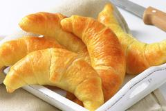 Fresh butter crescent rolls (croissants) on white wooden tray Stock Photos
