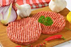 raw hamburger patties and vegetables on cutting board - stock photo