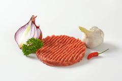 raw hamburger patty, onion and garlic - stock photo