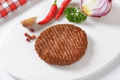 Grilled Beef Burger Patty on cutting board - stock photo